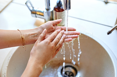 Buy stock photo Cropped shot of a woman washing her hands at the sink in the kitchen at home