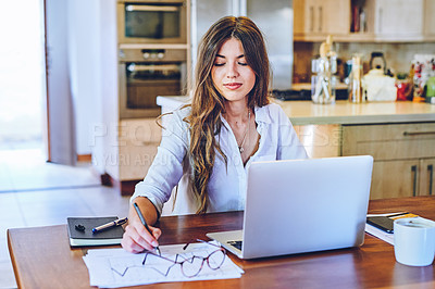 Buy stock photo Shot of a young woman using a laptop and going through paperwork at home