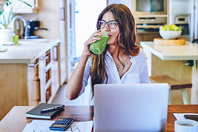 Buy stock photo Shot of a young woman having a healthy smoothie while working from home