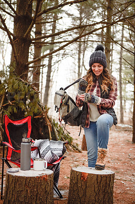 Buy stock photo Shot of a young woman camping in the wilderness during winter