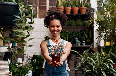 Buy stock photo Portrait of a young woman holding a potted plant while working in a garden centre