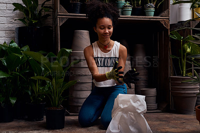 Buy stock photo Shot of a young woman holding soil while working in a garden centre