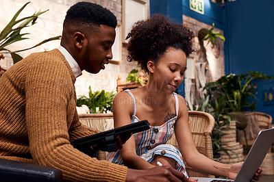 Buy stock photo Shot of a young man and woman using a laptop and digital tablet while working in a garden centre