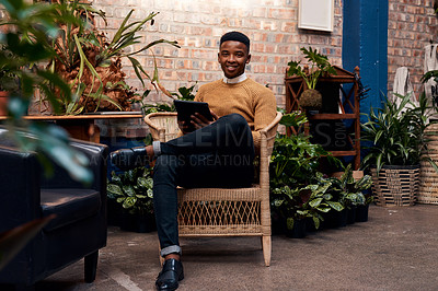 Buy stock photo Shot of a young man using a digital tablet while working in a garden centre