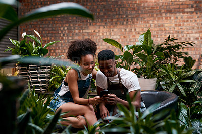 Buy stock photo Shot of a young man and woman using a smartphone while working in a garden centre