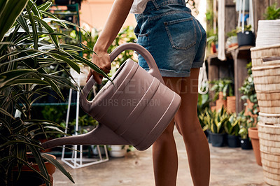 Buy stock photo Shot of an unrecognisable woman holding a watering can while working in a garden centre
