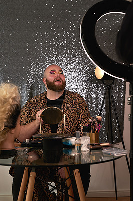 Buy stock photo Shot of a young man recording himself applying theatrical makeup in a studio