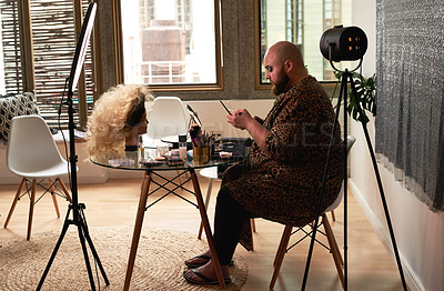 Buy stock photo Shot of a young man using a smartphone while recording himself applying theatrical makeup in a studio