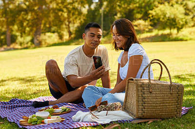 Buy stock photo Shot of a man showing his girlfriend something on his cellphone while on a picnic at the park