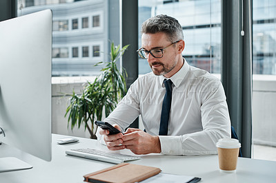 Buy stock photo Shot of a mature businessman using a cellphone while working in an office