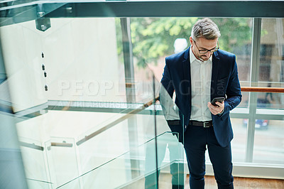 Buy stock photo Shot of a mature businessman using a cellphone while walking up a staircase in an office
