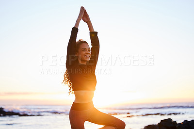 Buy stock photo Shot of an attractive young woman doing yoga alone on the beach at sunset