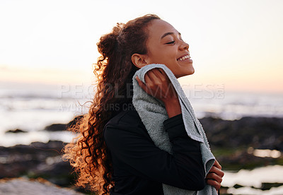 Buy stock photo Shot of an attractive young woman standing alone and using a towel after a sunset yoga session on the beach