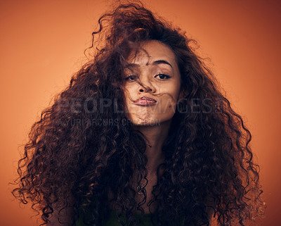 Buy stock photo Shot of a woman with curly hair posing against an orange background