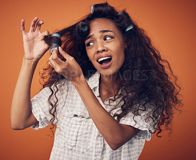Buy stock photo Shot of a woman pulling hair rollers out of her hair