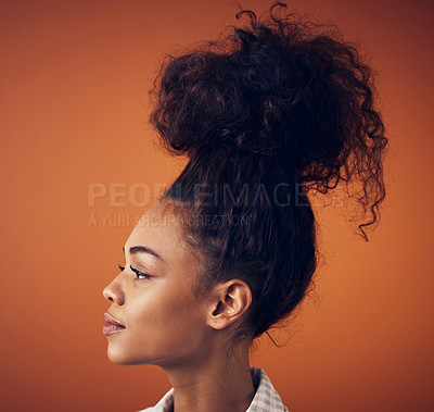 Buy stock photo Shot of a young woman wearing her hair in a bun against an orange background