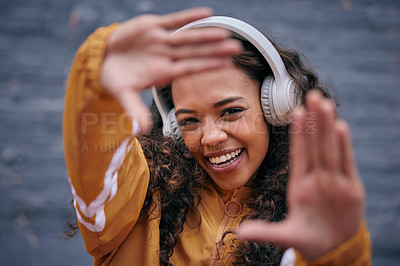 Buy stock photo Cropped shot of a beautiful young woman wearing headphones while standing outside