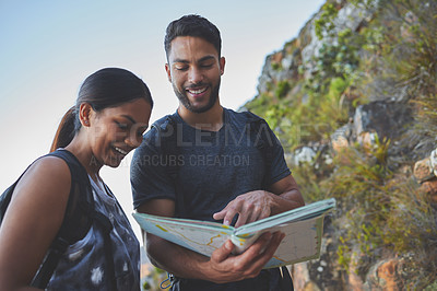 Buy stock photo Shot of a young couple using a guide book to complete a hike in a mountain range