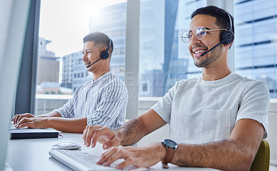 Buy stock photo Shot of two business colleagues working together at their desks in their office