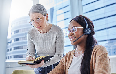 Buy stock photo Shot of a young businesswoman going over some work with her manager