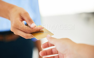 Buy stock photo Shot of two people exchanging bank cards to complete a purchase