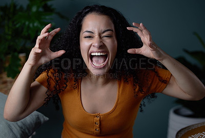 Buy stock photo Shot of a young woman feeling angry at home