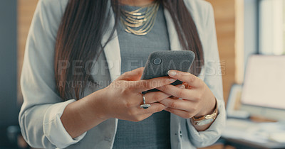Buy stock photo Shot of a businesswoman using her smartphone in her office