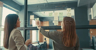 Buy stock photo Shot of two businesswomen brainstorming ideas in their office