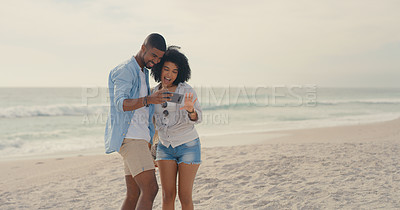 Buy stock photo Shot of a man showing his girlfriend something on his cellphone while at the beach