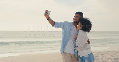 Buy stock photo Shot of a young couple taking a selfie while spending the day at the beach