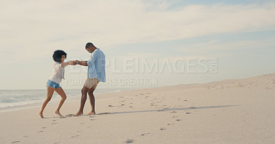 Buy stock photo Shot of a young couple sharing a dance at the beach