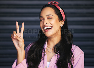 Buy stock photo Cropped portrait of an attractive young woman making the peace sign while posing against a grey background