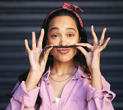 Buy stock photo Cropped portrait of an attractive young woman making a moustache with her hair while posing against a grey background