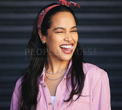 Buy stock photo Cropped portrait of an attractive young woman winking playfully while posing against a grey background