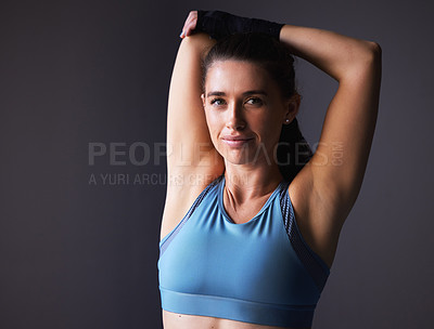 Buy stock photo Shot of a young woman stretching her arms against a grey background