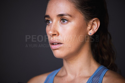 Buy stock photo Shot of a sporty young woman standing against a grey background