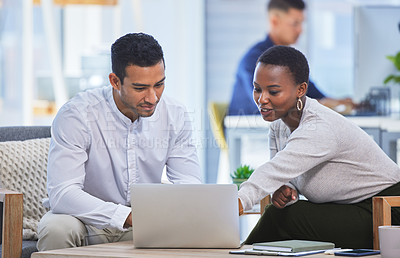Buy stock photo Shot of two businesspeople discussing something on a laptop while sitting together in an office
