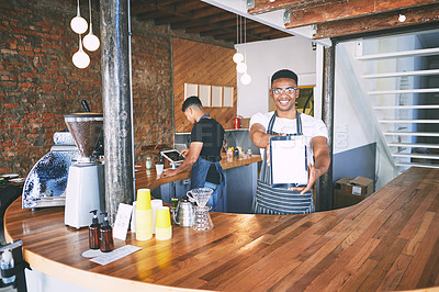 Buy stock photo Shot of a young man showing a digital tablet with a blank screen while working in a cafe