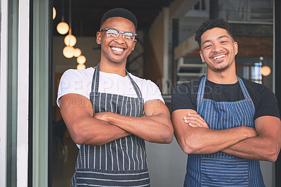 Buy stock photo Shot of two confident young men standing at the entrance of their cafe