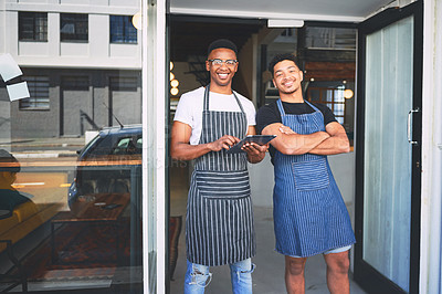 Buy stock photo Shot of two young men using a digital tablet while standing at the entrance of a cafe