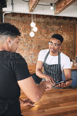 Buy stock photo Shot of a young man using a digital tablet while serving a customer in a cafe