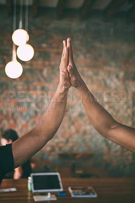 Buy stock photo Shot of two unrecognisable men giving each other a high five while working in a cafe