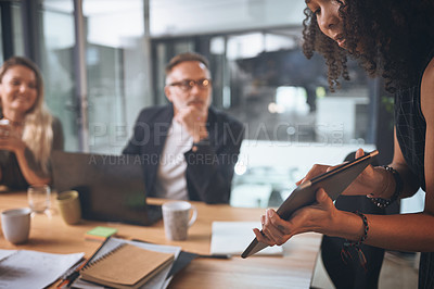 Buy stock photo Shot of a young businesswoman using a digital tablet while delivering a presentation in the boardroom of a modern office