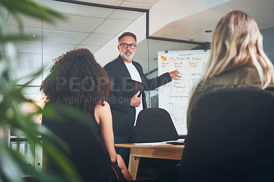 Buy stock photo Shot of a mature businessman delivering a presentation in the boardroom of a modern office