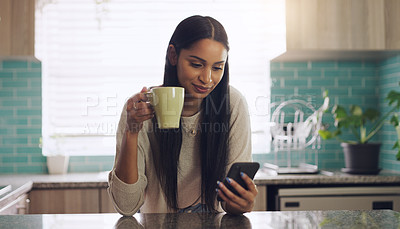Buy stock photo Shot of a young woman drinking coffee while using her smartphone at home