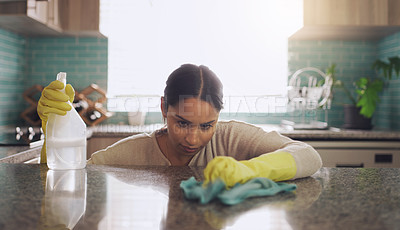Buy stock photo Shot of a young woman scrubbing down her kitchen counter at home