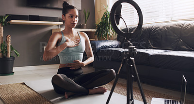 Buy stock photo Shot of a young female fitness trainer getting ready to live stream her workout at home