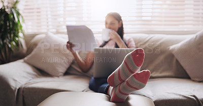Buy stock photo Shot of a young businesswoman drinking a cup of coffee while reading paperwork at home