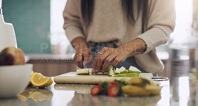 Buy stock photo Shot of an unrecognizable woman cutting fruit to prepare a smoothie on her kitchen at home