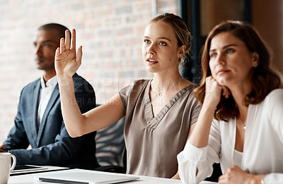 Buy stock photo Shot of an attractive young businesswoman sitting with her coworkers and raising her hand to ask a question